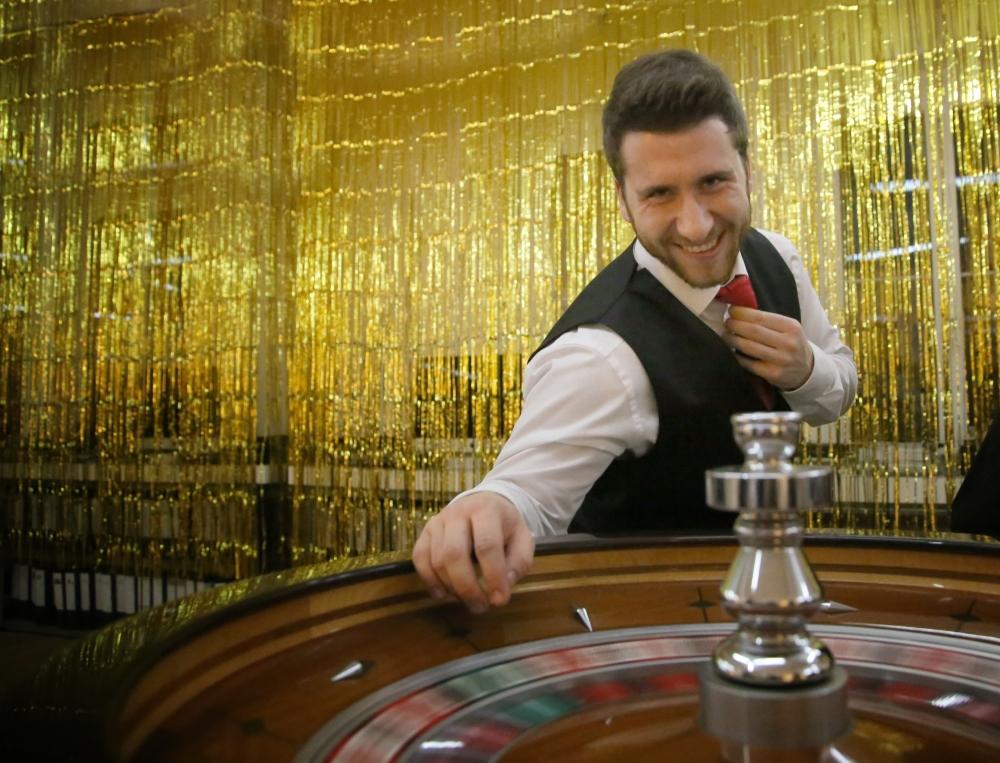 Roulette Croupier vor goldenem Vorhang
